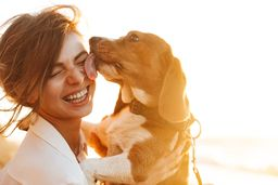 A woman holds a puppy smiling while it licks her face. She is very happy after starting self-esteem therapy in Texas with online counselor Addie at Everyday Bravery