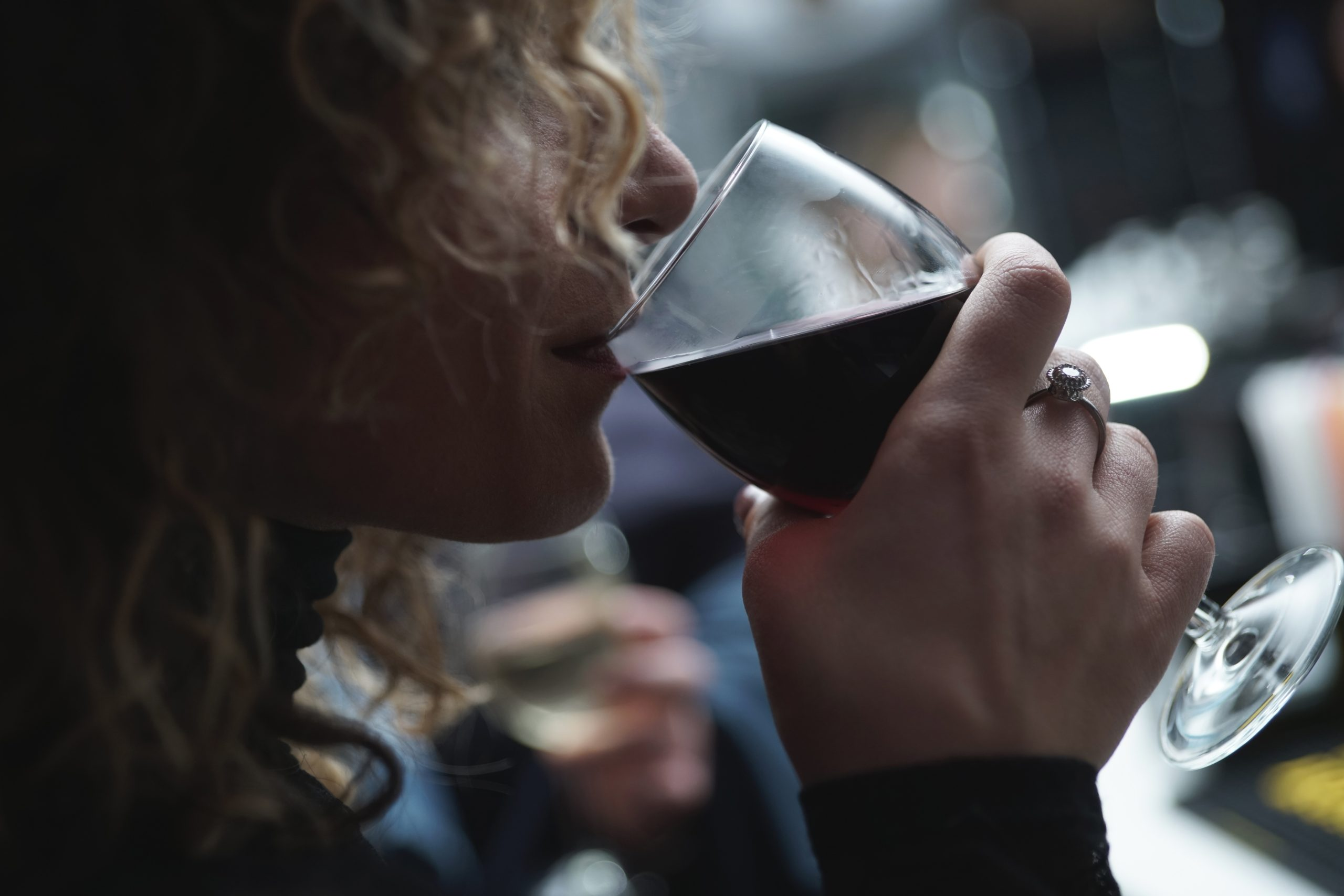 A woman drinks a glass of wine with a soft smile on her face. She has started online anxiety treatment in Texas with Everyday Bravery. You can get online counseling in Texas with Addie too!