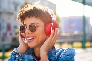 A woman laughing wearing headphones is feeling happy again after starting online anxiety treatment in Texas with Everyday Bravery Counseling and Therapy.