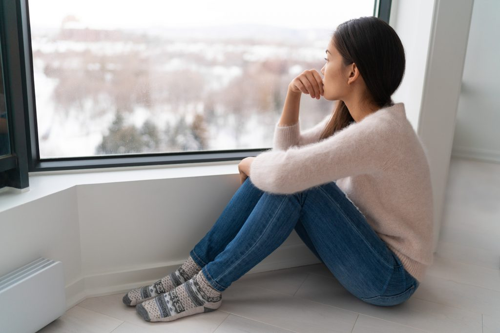 A woman sits next to a window looking distraught. She is ready to start online trauma therapy in Texas with online counselor in Texas, Addie, from Everyday Bravery.